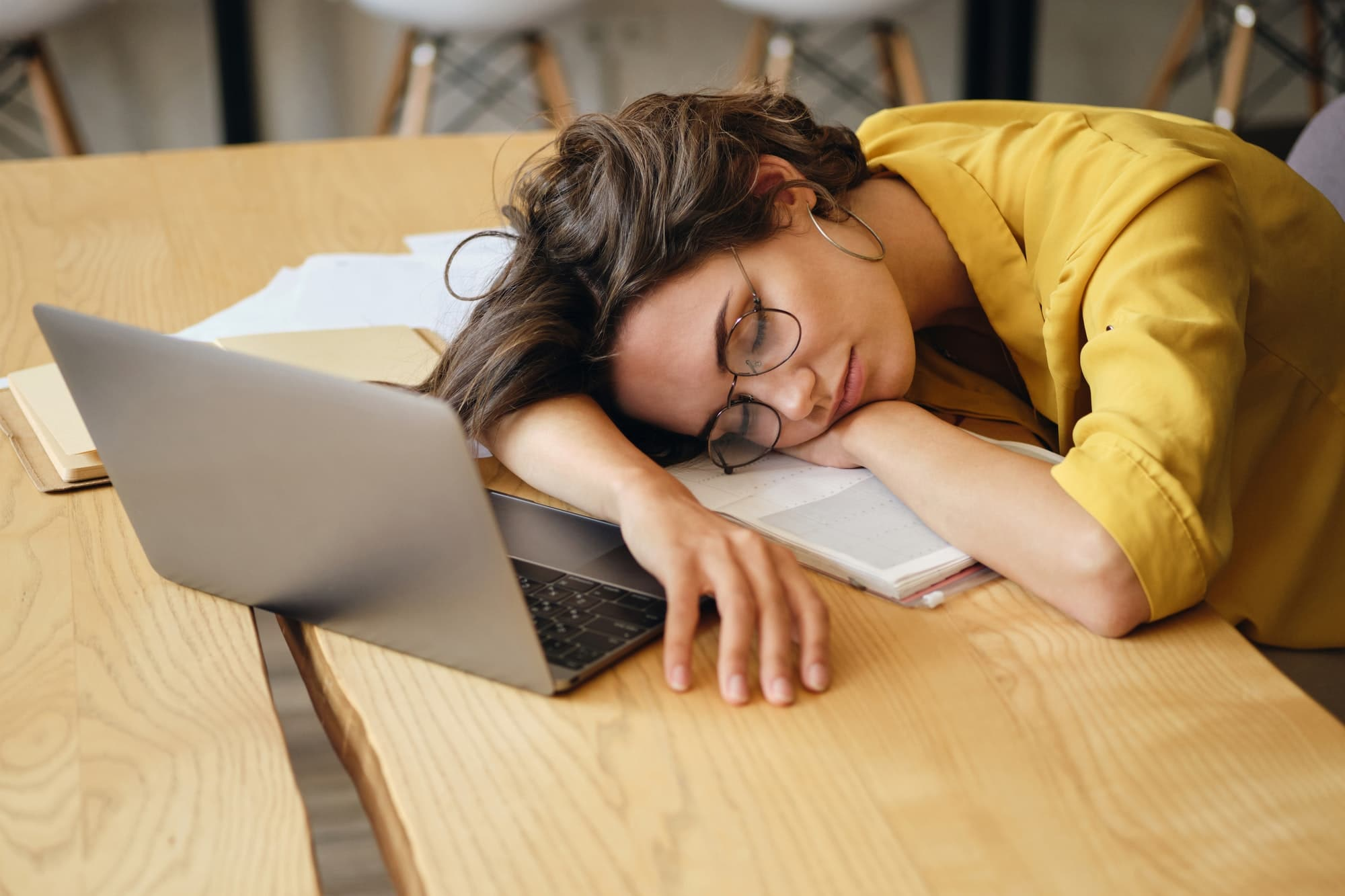 Tired woman in eyeglasses fall asleep on desk with laptop and documents under head at workplace
